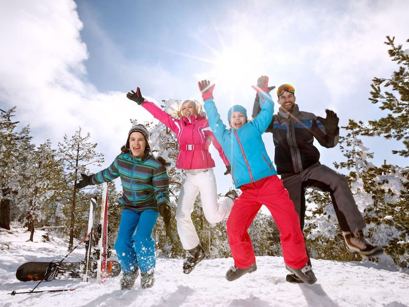 Happy family on skiing jumping on snow in mountain